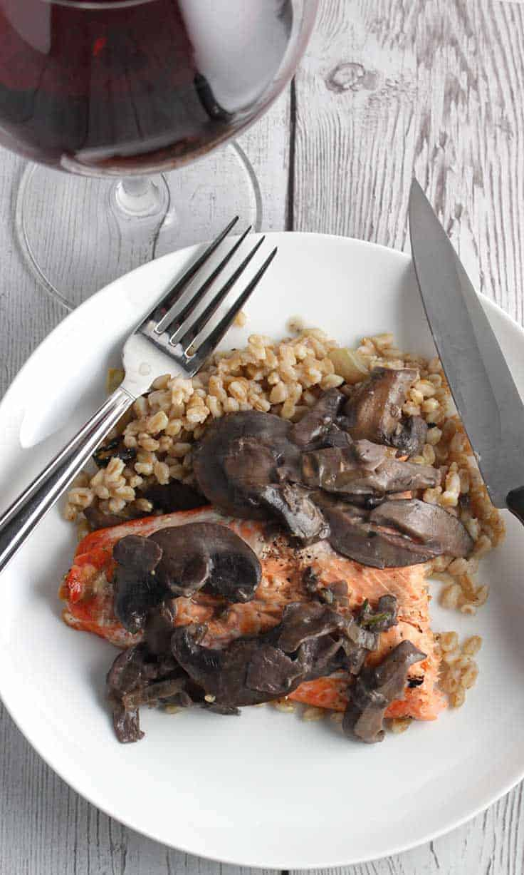 grilled salmon with mushroom sauce on a white plate, served with red wine.
