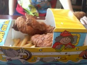 chicken fingers and fries in a boat shaped serving plate.
