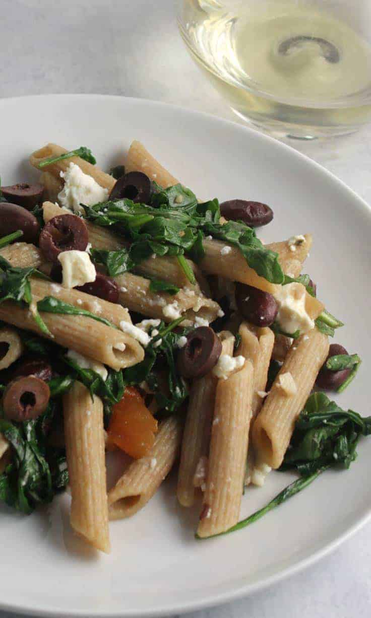 penne with arugula, garlic and beans on a plate.