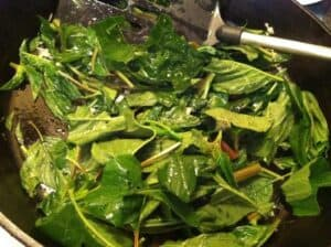 callalloo greens being sauted in a skillet