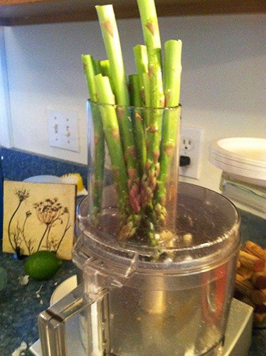 asparagus getting prepared for a raw salad with parmesan cheese.