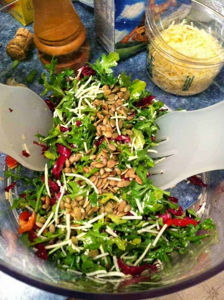 Tuscan Inspired Arugula Salad getting tossed. Cooking Chat recipe.
