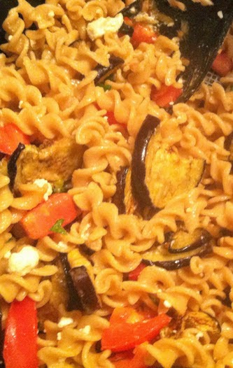 fusilli getting stirred with grilled eggplant, tomatoes and feta cheese, to be served with grilled swordfish. Cooking Chat recipe.