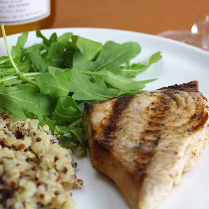 grilled swordfish plated with quinoa and arugula.