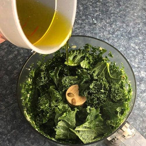 drizzling olive oil into blender for kale pesto.