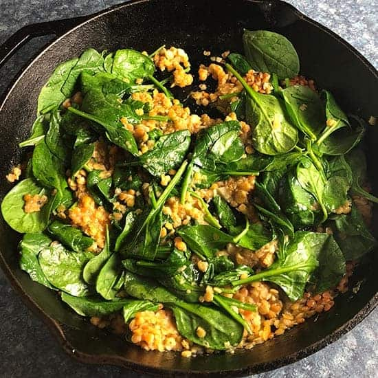 skillet with spinach and red lentils.
