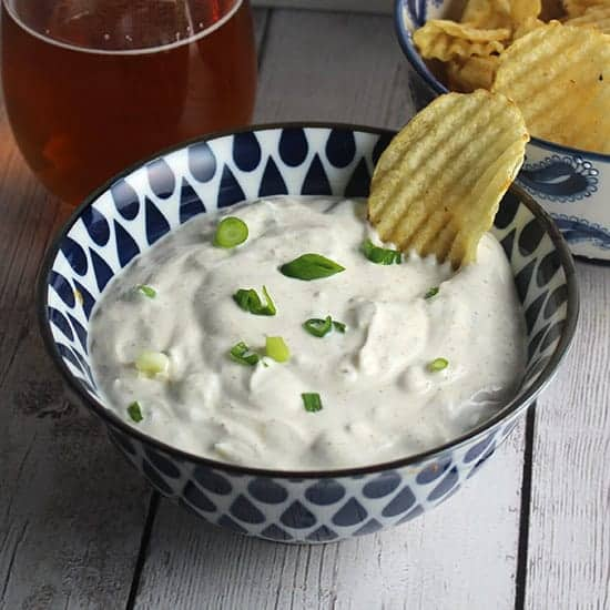 bowl of green onion dip next to a bowl of chips and a beer.