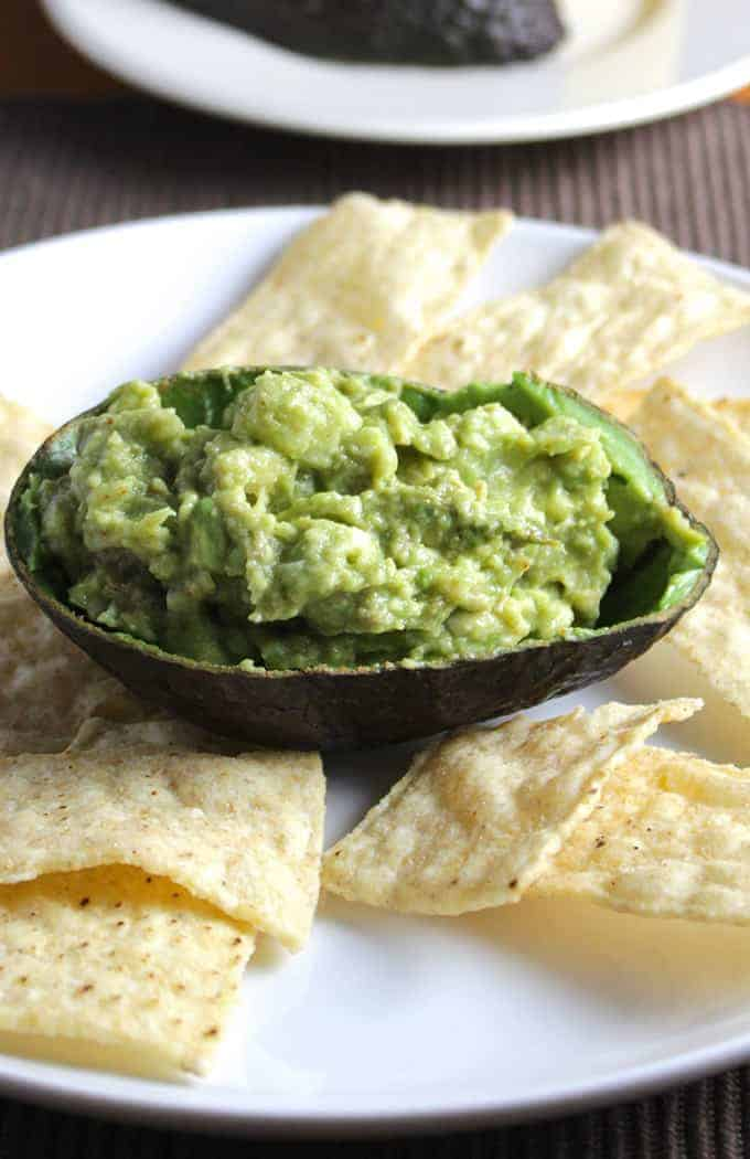 Keep the avocado peels for serving your guacamole! Simple Guacamole recipe from Cooking Chat.