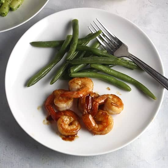 sauteed shrimp on a plate with green beans.