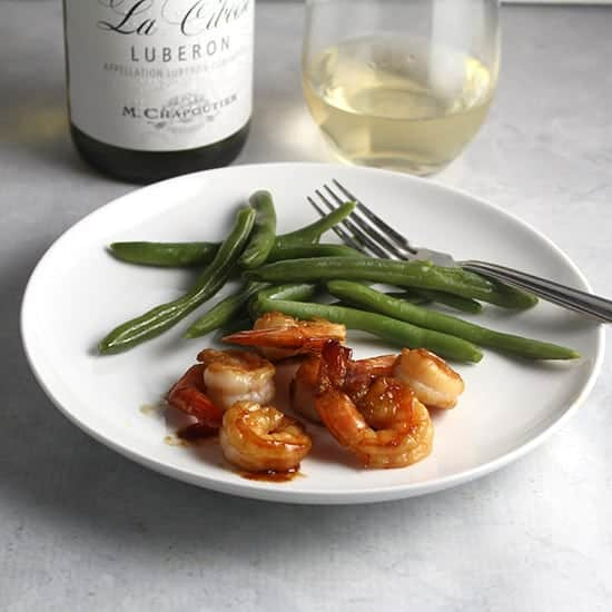 white Rhone wine served with a plate of sautéed shrimp.