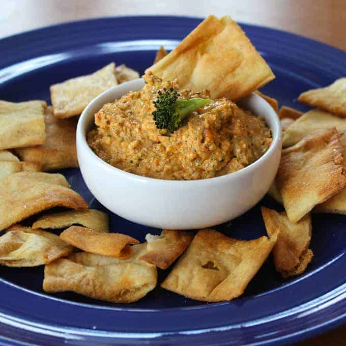 small bowl with roasted broccoli dip and chips on the side.