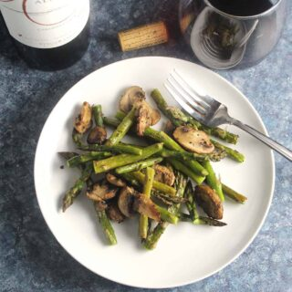 roasted asparagus with mushrooms on a white plate.