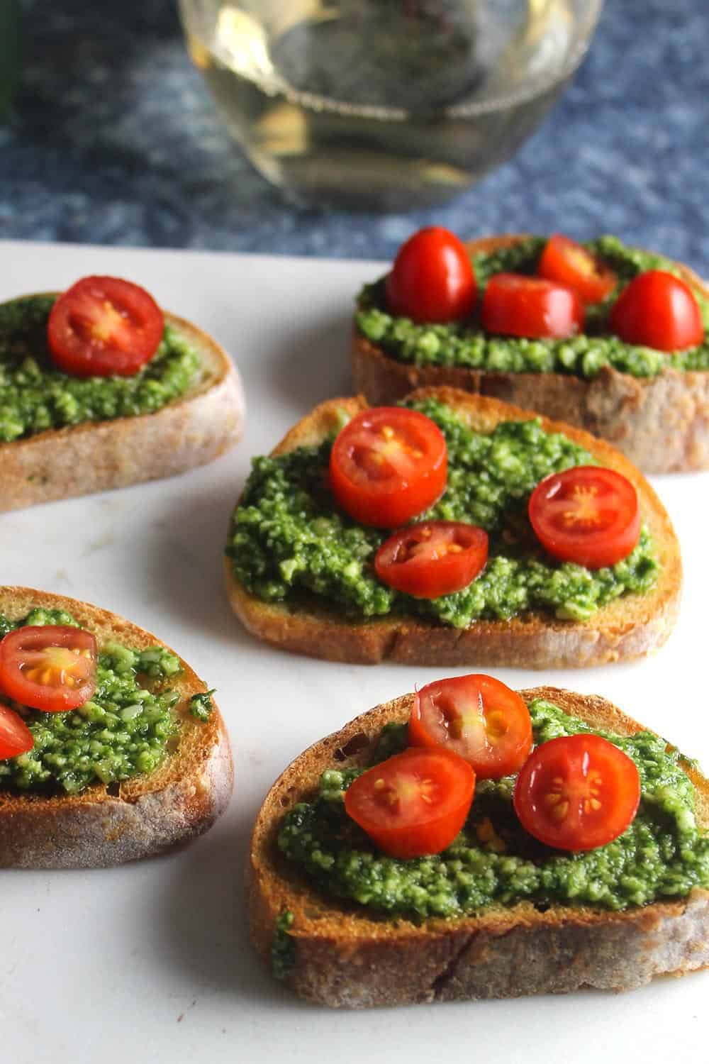basil pesto crostini served topped with tomatoes