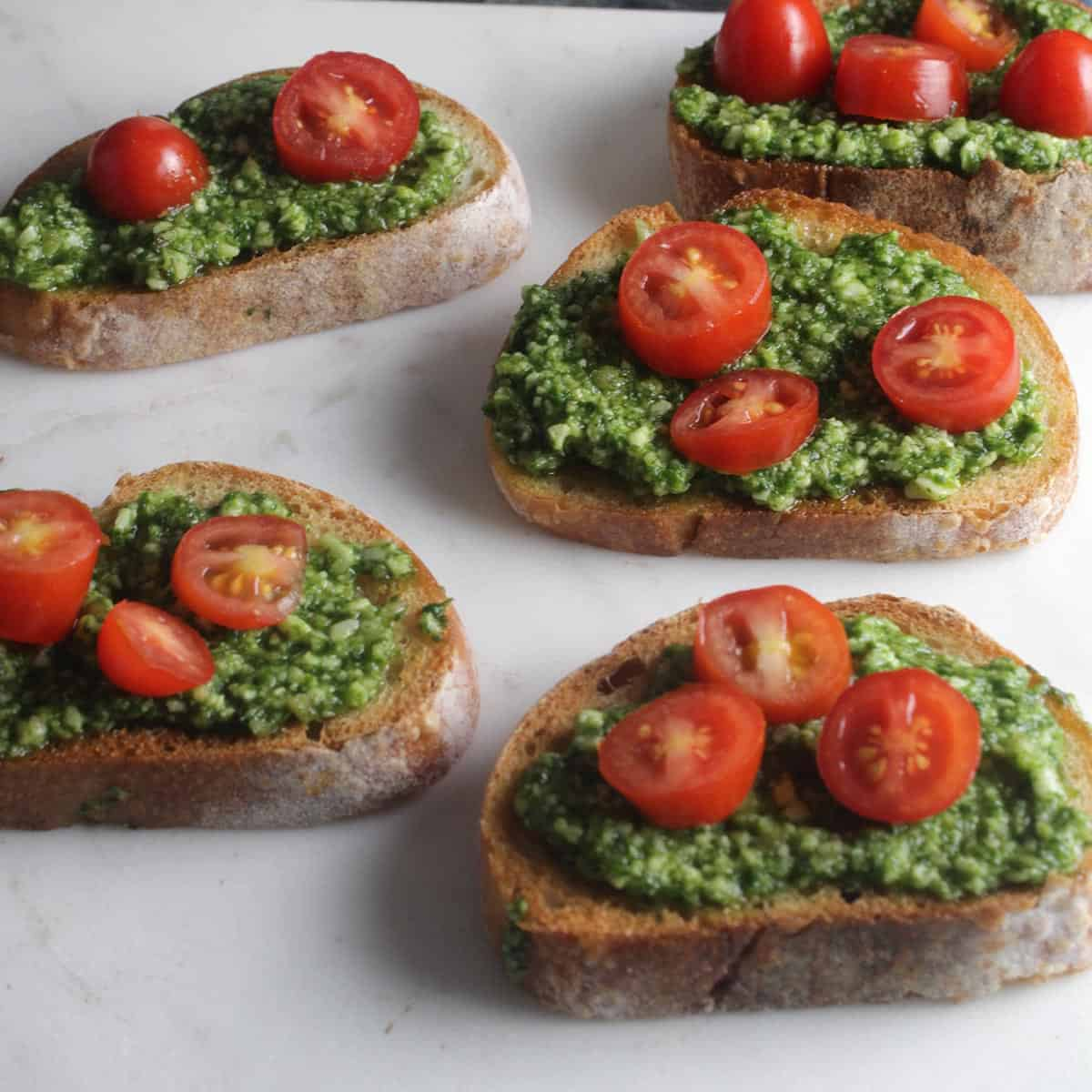 crostini topped with pesto and red tomatoes