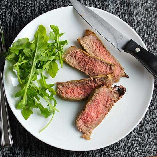 slices of NY strip steak plated with arugula.