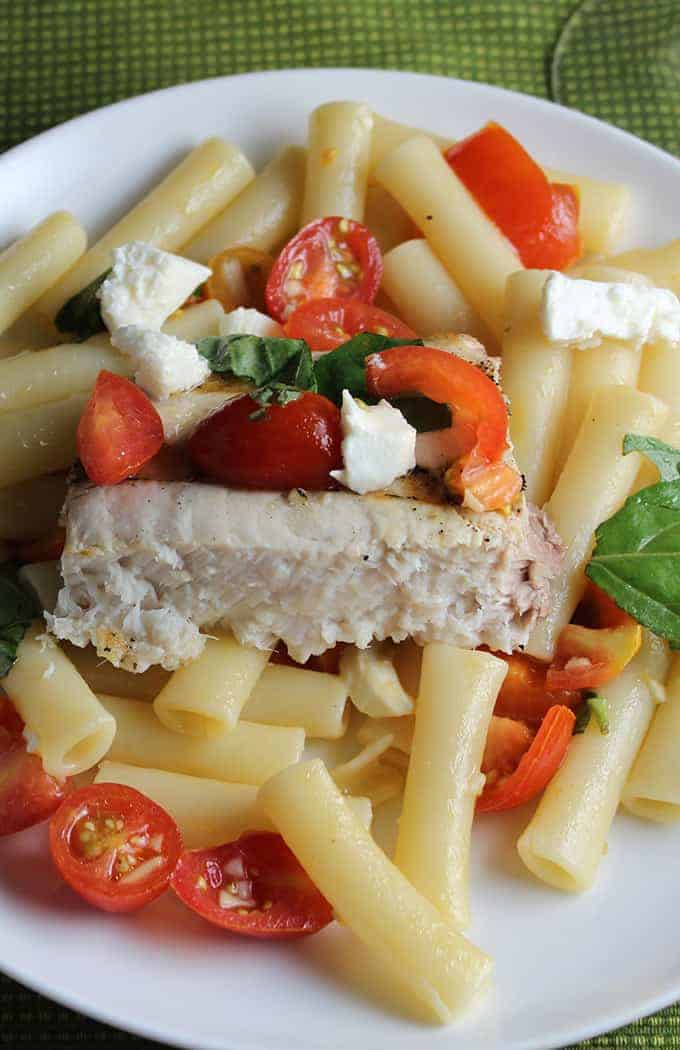 grilled swordfish plated with pasta, topped with tomatoes and mozzarella cheese.