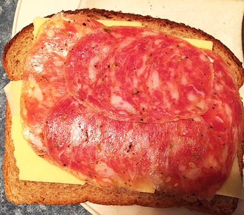 Making grilled cheese and salami sandwich