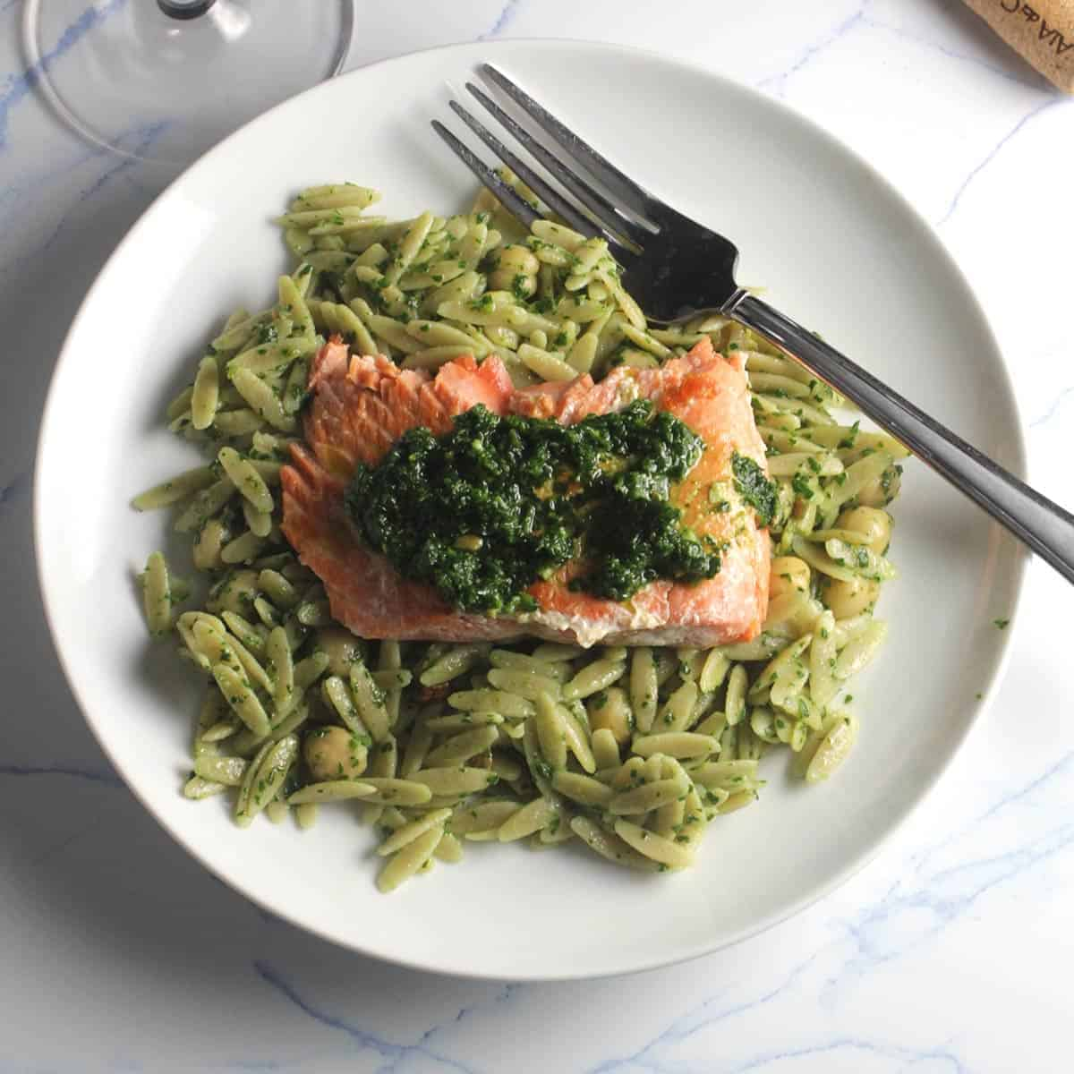 plate of orzo with salmon on top.