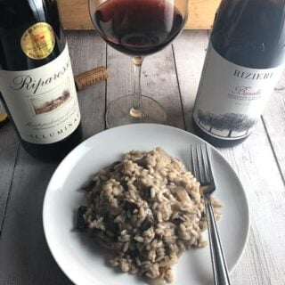 mushroom risotto on a plate with two bottles of Italian red wine.