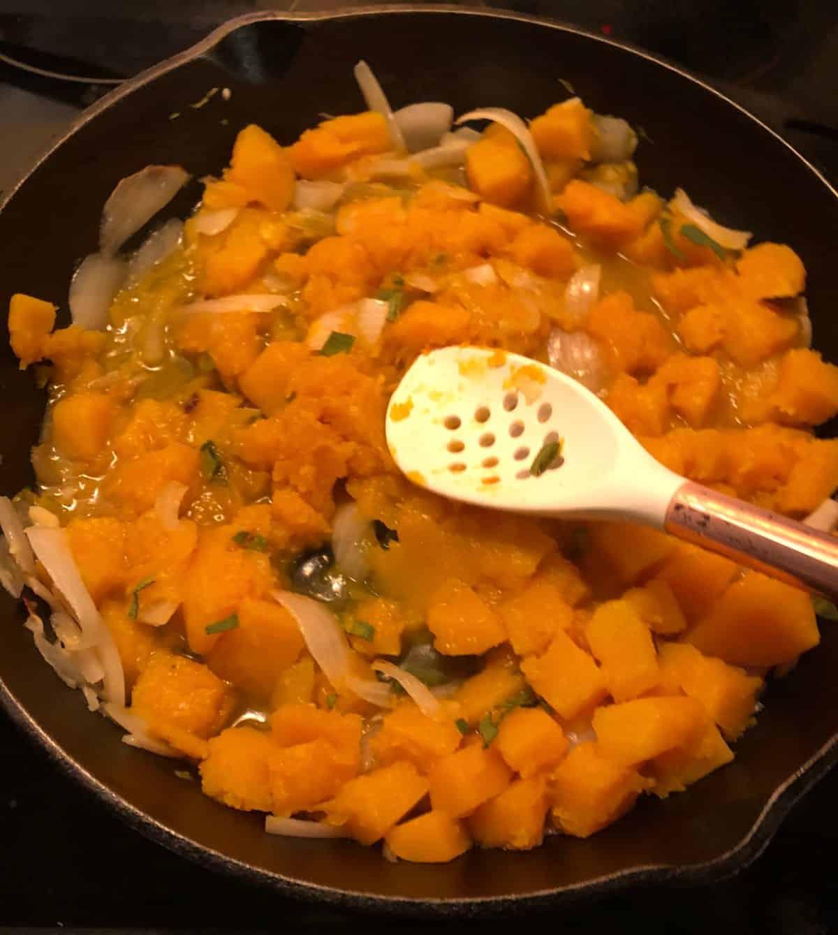 stirring butternut squash in a skillet