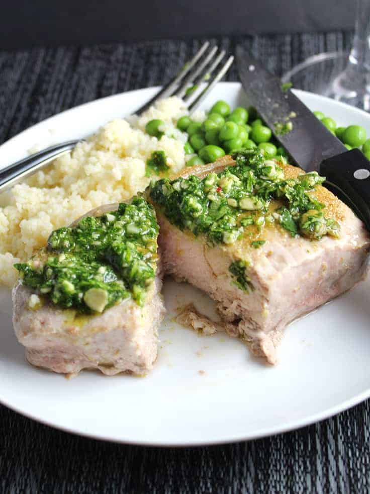 Zesty cilantro pesto tops roasted pork chops for an easy and flavorful meal.