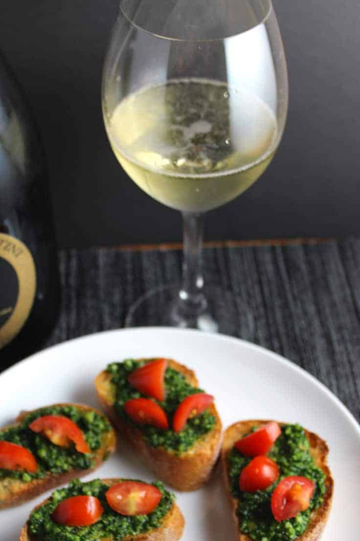 Sparkling wine refreshes the palate after a bite of zesty kale pesto, making it a great kale pesto crostini wine pairing for a festive holiday gathering.