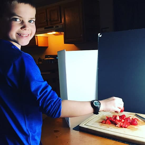 young sous chef helping to make quinoa with salmon and strawberries.