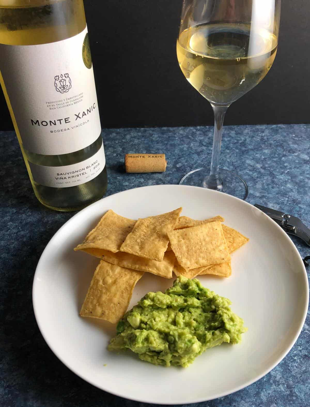 guacamole served with chips and a white wine.