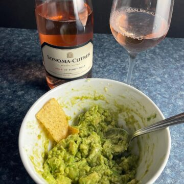 bowl of guacamole with rosé wine.