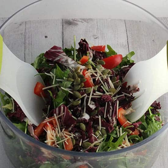 Tossing arugula salad with maple vinaigrette