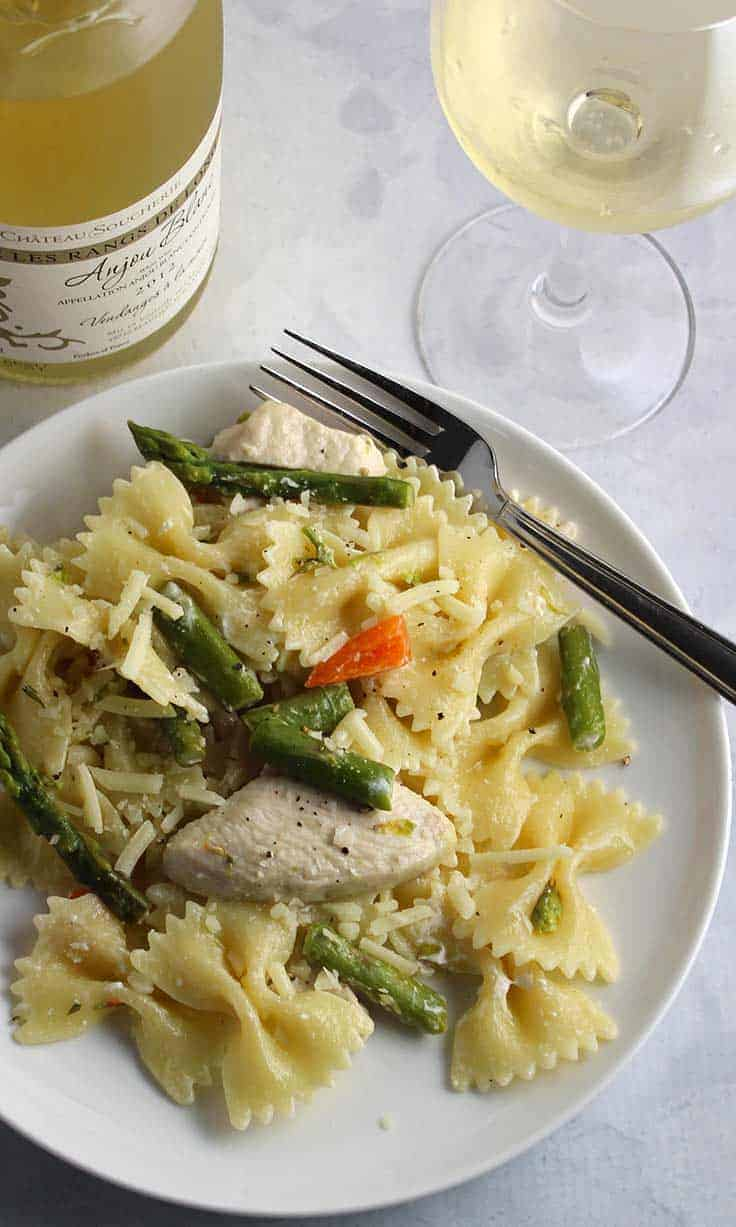 Asparagus Chicken Bowtie Pasta on a plate with white wine.