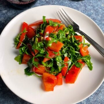 arugula sautéed with red peppers and served on a white plate.
