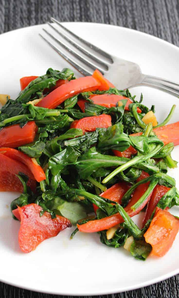 sautéed arugula with red bell peppers on a white plate.