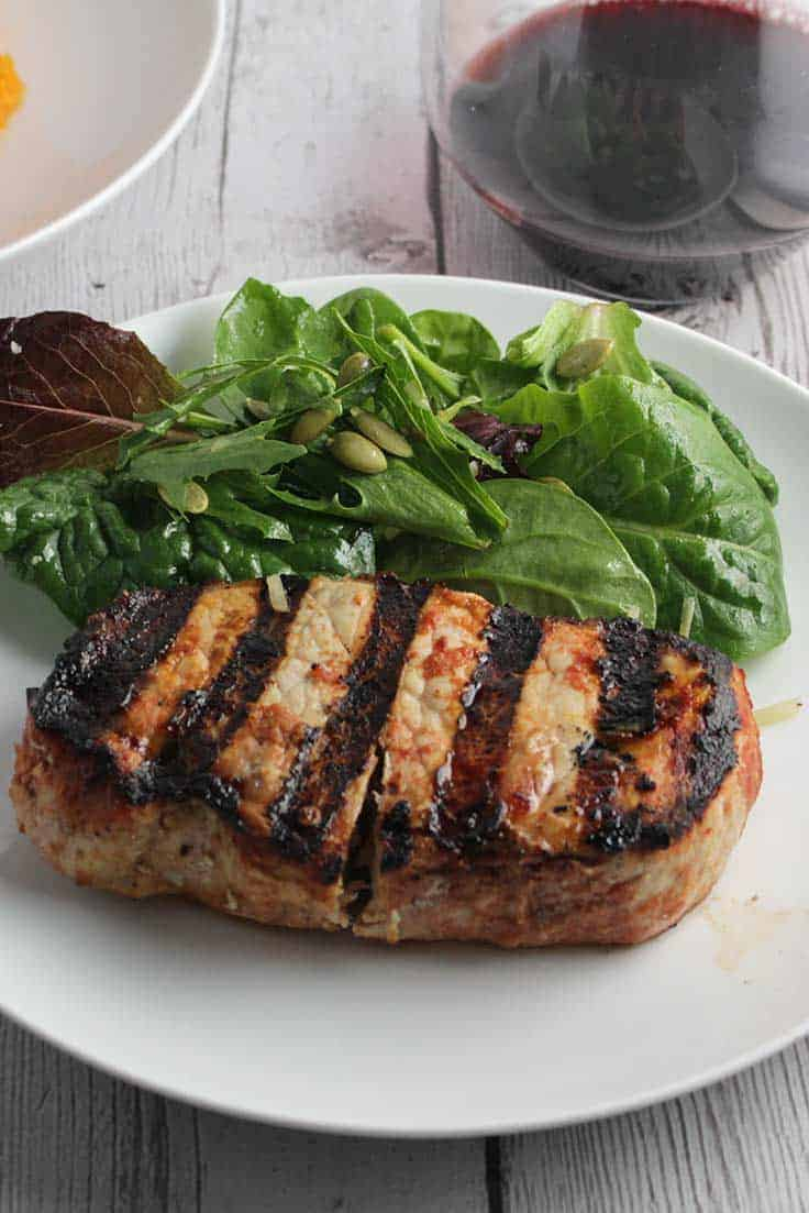 grilled chipotle pork chops on a plate with salad.