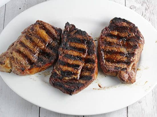 grilled ribeye steaks resting on platter.
