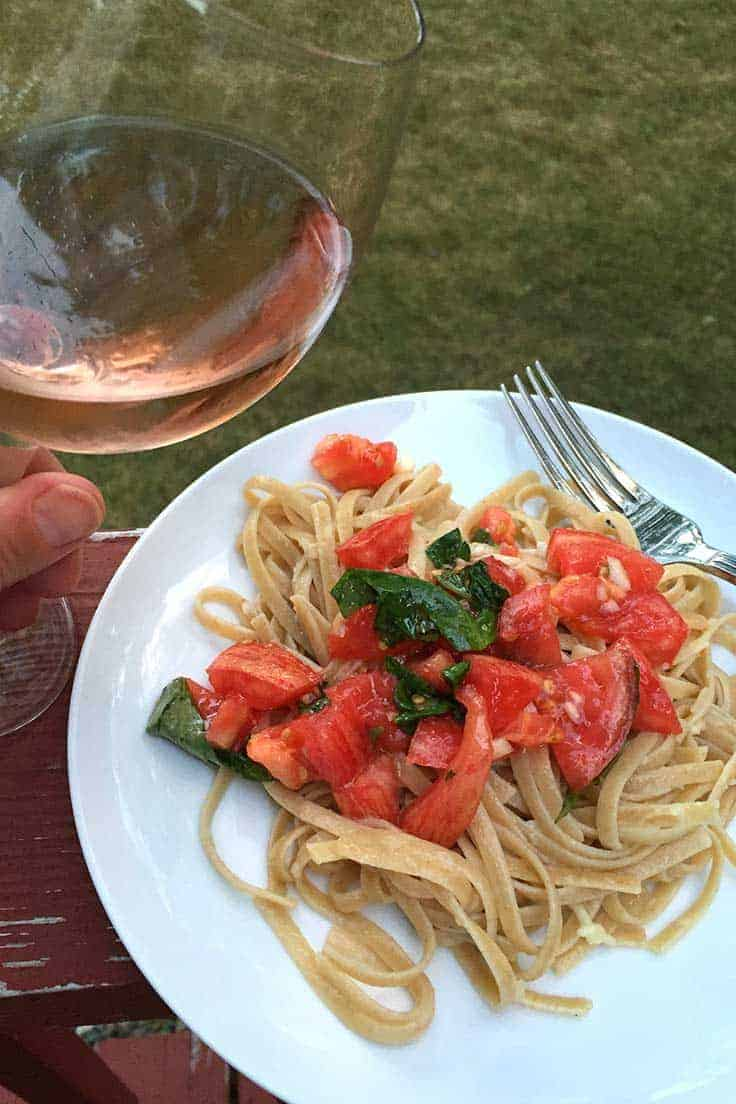 plate of pasta with fresh tomatoes and a glass of rosé wine.