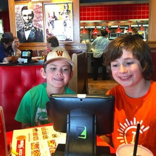 Boys checking out the menu with allergy friendly options at Red Robin.