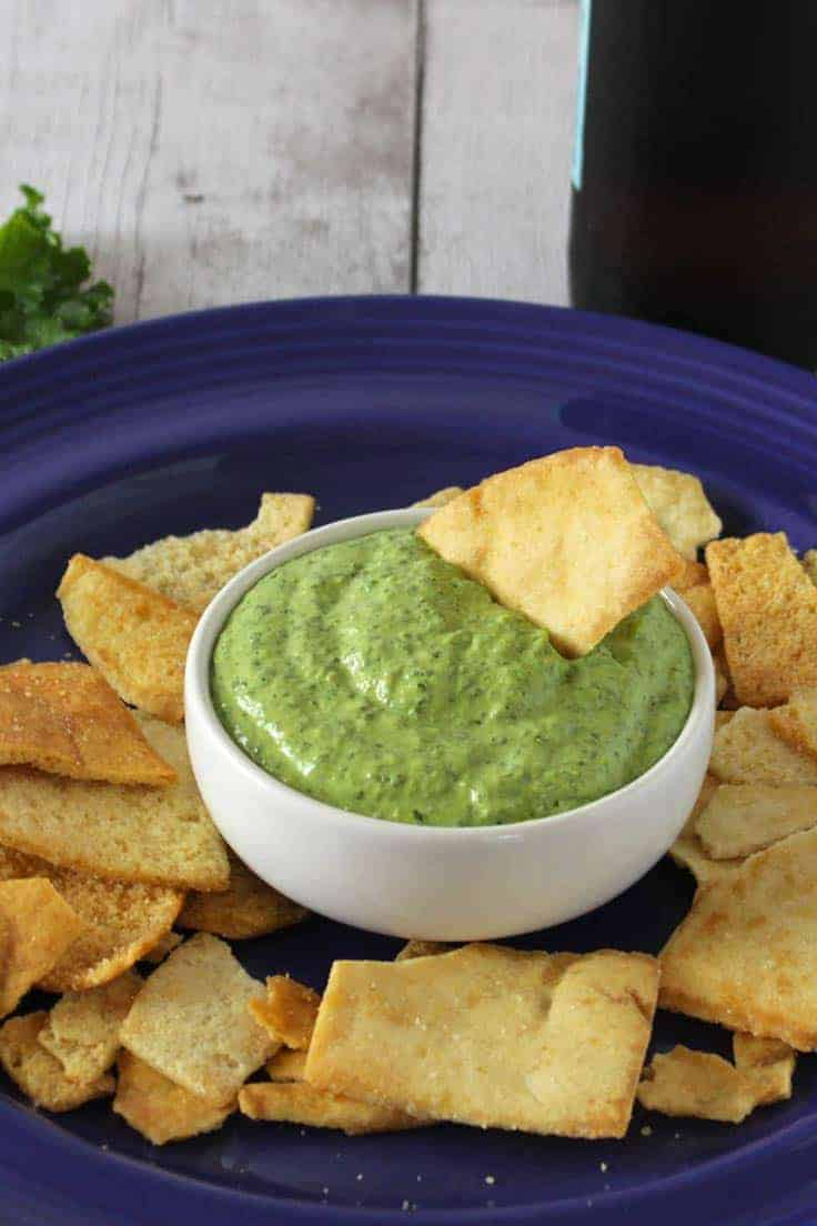 bowl of kale pesto dip served with pita chips.