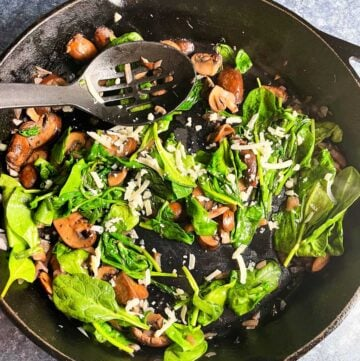 sautéed spinach and mushrooms in a large black skillet, being stirred with a large spoon.