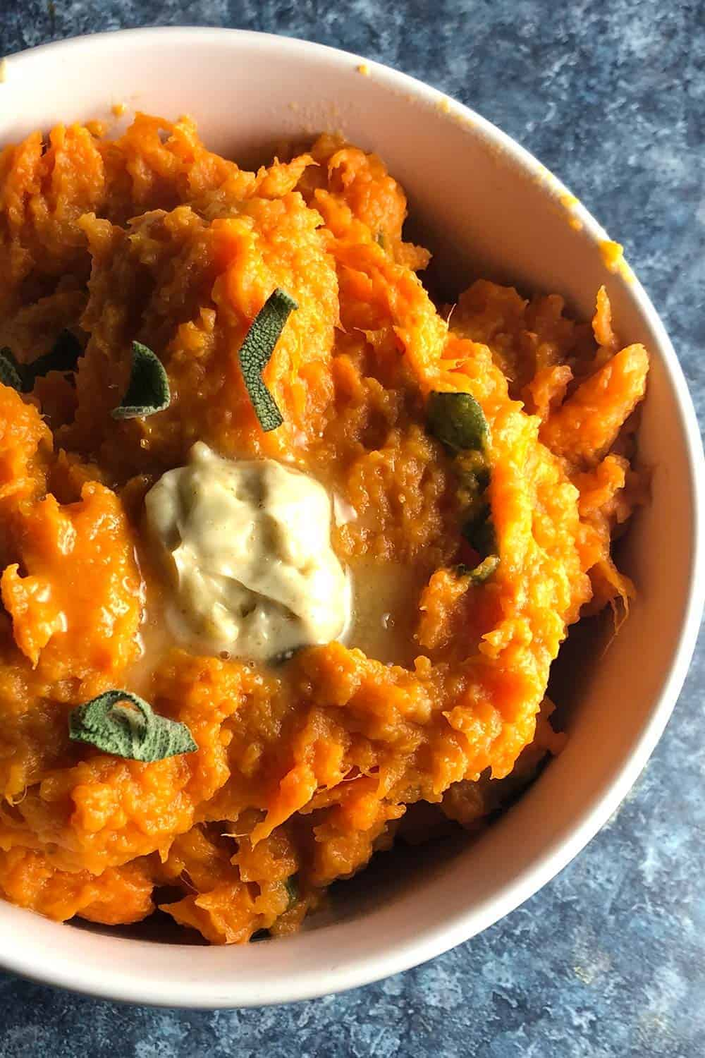 mashed sweet potatoes in a bowl with cumin sage butter.