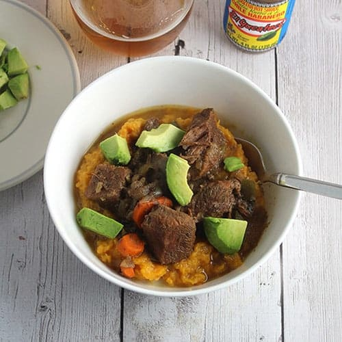 bowl of spicy beef stew with avocado slices on top.