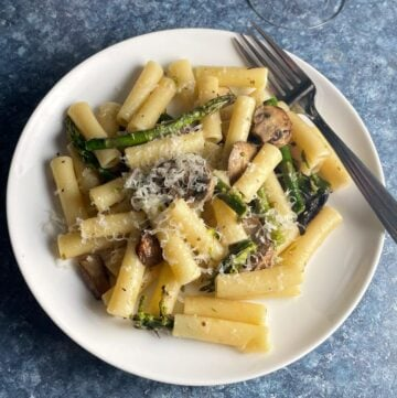 asparagus and mushroom pasta on a white plate topped with grated Parmesan cheese.