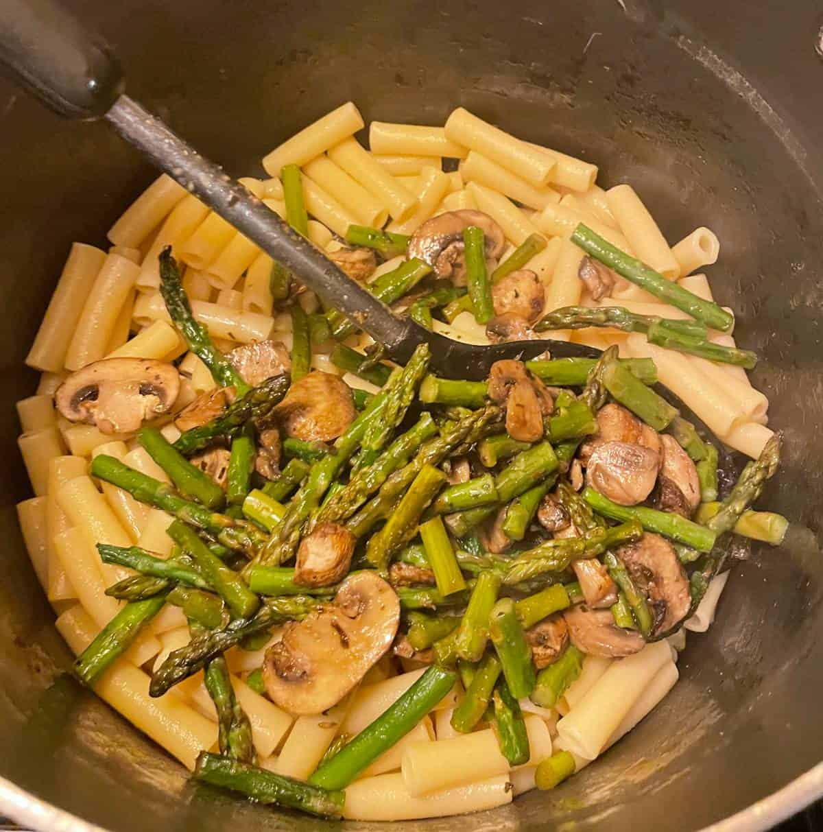combining asparagus and mushrooms with pasta in a silver pan.