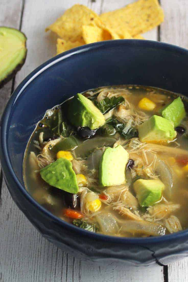 chicken simmers with chipotle peppers and black beans for a flavorful and healthy soup, topped with avocado.