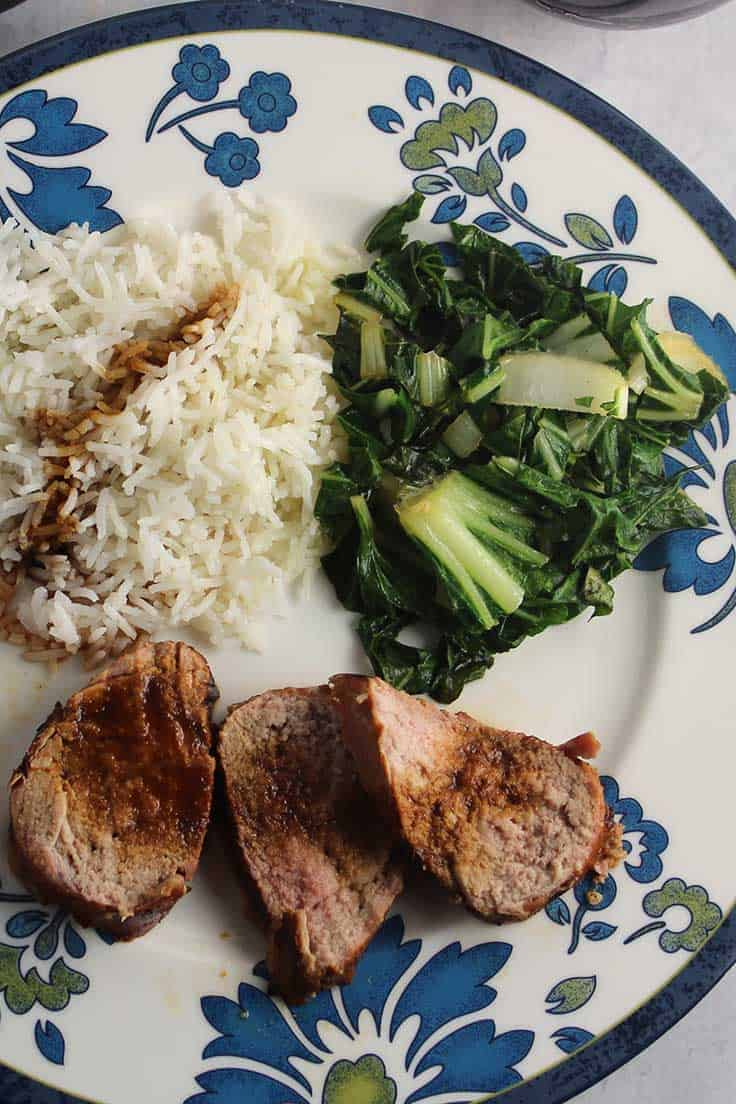 Grilled Asian Pork Tenderloin on a plate with rice and bok choy.