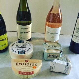a selection of French wines and cheeses ready for sampling.