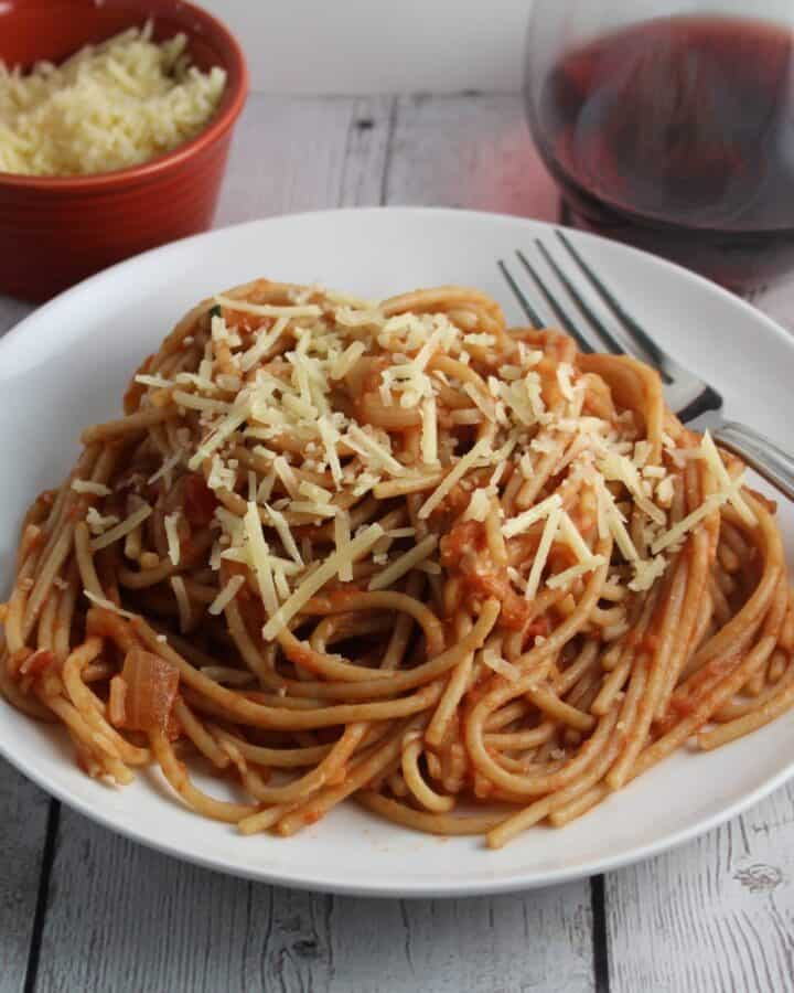 spaghetti with tomato apple pasta sauce on a white plate