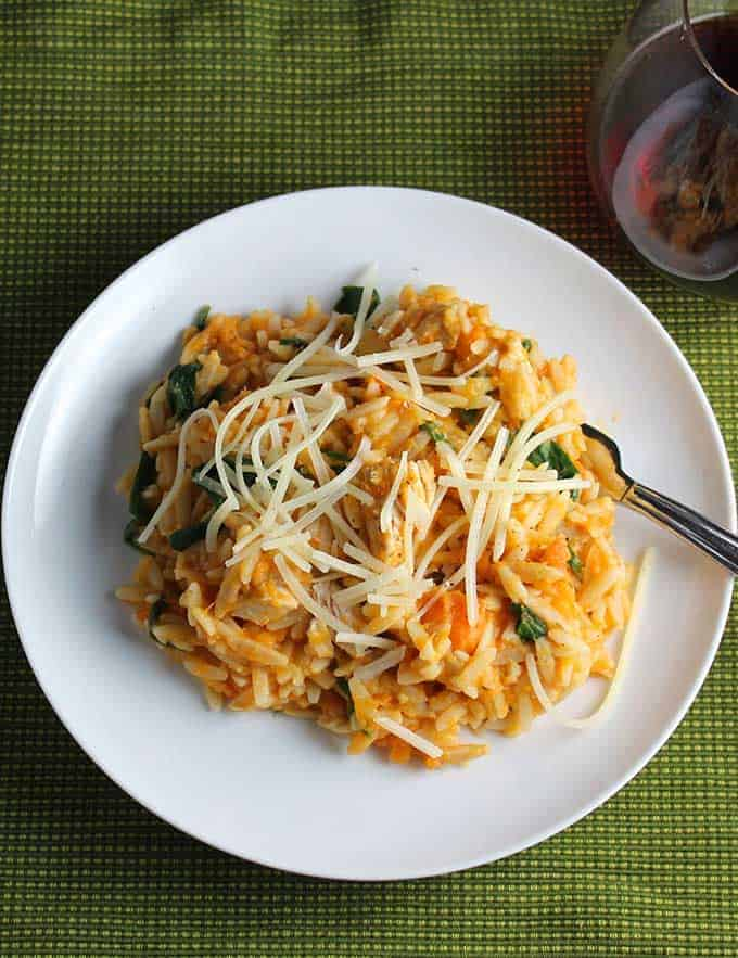 Orzo with leftover turkey and sweet potatoes on a white plate, served with a glass of red wine.