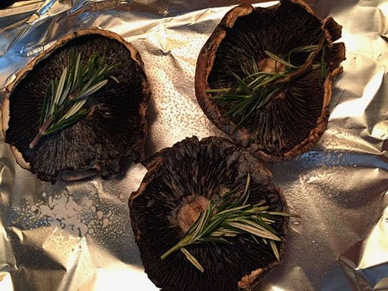 Portobello mushrooms ready to roast with sprigs of rosemary.