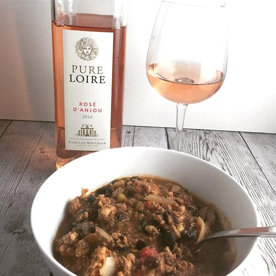 a rosé wine served with a bowl of black bean turkey chili.